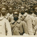 """Bildpostkarte, ungelaufen. Gruppe von sechs afrikanischen Soldaten, vermutlich kurz nach der Gefangennahme aufgenommen. Rückseite mit handschriftlicher Notiz: """"Senegal-Neger an der Westfront"""". Sammlung Markus Kreis."""