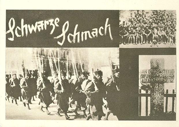 """""""Schwarze Schmach"""". Ansichtskarte zur Ausstellung """"1918"""", die in Wien vom Dezember 1943 bis Februar 1944 präsentiert wurde. Ansichtskarte ungelaufen. Sammlung Markus Kreis.  """"Schwarze Schmach"""" war nach Ende des Ersten Weltkriegs eine von Deutschland ausgehende internationale Kampagne gegen den Einsatz französischer Kolonialtruppen während der Rheinlandbesetzung.  Die Kampagne wurzelt aber bereits in der deutschen Reaktion auf den Einsatz """"schwarzer"""" Kolonialtruppen vor und während des Ersten Weltkriegs an der Westfront. Von der NSDAP aufgenommen, gehörte die Kampagne zum festen Instrumentarium bis in den Zweiten Weltkrieg hinein, mit Auswirkungen und """"Wiederbelebungen"""" in der Zeit nach 1945."""