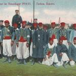 """""""Kriegsgefangene im Sennelager 1914/15. Turkos, Zuaven."""" Ansichtskarte, gelaufen aus dem Sennelager als Feldpost im März 1915. Eine bildidentische, ungelaufene Ansichtskarte mit dem Titel """"Kriegsgefangene 1914/15. Turkos, Zuaven"""" enthält auf der Rückseite die Angabe """"H. Schanz, Soest"""". Sammlung Detlev Brum. """"Turkos"""" war eine gebräuchliche Sammelbezeichnung für nord- und westafrikanische, muslimische Soldaten. Ernst Mehlich, Redakteur der sozialdemokratischen Dortmunder Arbeiter-Zeitung, berichtet über die afrikanischen Kriegsgefangenen in der Senne: """"Im Lager der Belgier sind auch die afrikanischen Truppen untergebracht. Diese verlassen ihre Zelte oder Baracken nur wenn die Sonne scheint. Die braunen Söhne Marokkos sind unser rauhes Klima nicht gewöhnt. Sie vergraben sich daher im Stroh und hüllen sich in ihre warmen Schlafdecken ein."""""""