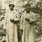 Ansichtskarte, ungelaufen, ohne Datum, keine weiteren Angaben. Sammlung Markus Kreis. Die Ansichtskarte zeigt zwei kriegsgefangene afrikanische Soldaten, die als Trophäe inszeniert werden. Jeweils die linke Hand, an der die Soldaten Ringe und Armband tragen, wird demonstrativ hervorgehobenen. Ringe und Armbänder sind zeitgenössisch als Teil der deutschen Propaganda zu verstehen, die mit dem Vorwurf propagandistische Wirkung zu erzielen suchte, das die kolonialen Soldaten das Kriegsvölkerrecht missachteten und Finger, Ohren und Köpfe der Feinde abschnitten und/oder Ringe und Armbänder entwendeten. In der Realität sind jedoch keine ungewöhnlichen Verstöße gegen das Kriegsvolkerrecht bekannt geworden.