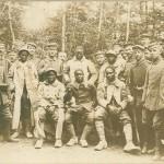 """Kriegsgefangene afrikanische oder afro-amerikanische Soldaten. Ansichtskarte, gelaufen als Feldpost im Juni 1918. Sammlung Markus Kreis. Handschriftlich auf der Rückseite der Helden-Gruß an die Angehörigen in der Heimat: """"Die Photographie da könnt Ihr unsere Gegner sehen lauter Schwarze. Die 6 Stück wurden von unser … Komp. gefangen und Photographiert."""" Im Unterschied zu den abwertenden """"Völkerschau""""- und """"Varieté""""-""""Neger""""-Inszenierungen kolonialer Kriegsgefangener handelt es sich hier ein Motiv aus der Gattung """"Trophäe"""", zwar auch fotografisch inszeniert, jedoch eher den Augenblick der Überlegenheit und eine besondere Lebenserinnerung dokumentierend."""