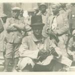 """Afrikanischer oder Afro-Amerikanischer Soldat mit Zylinder in Kriegsgefangenschaft. Ansichtskarte, ungelaufen. Sammlung Markus Kreis. In europäischen Ansichtskarten sind Zylinder-tragende Schwarze ein beliebtes Motiv, egal ob in Kolonial-, Missions-, Kitsch- oder Kriegsgefangenen-Ansichtskarten. Vermutlich soll damit die unterstellte kulturelle Differenz versinnbildlicht werden und der Zylindertragende der Lächerlichkeit preisgegeben werden. Da Zylinder nicht zur Basisausstattung von Soldaten zählte, darf hier vielleicht in Betracht gezogen werden, dass erst er Fotograf das """"Material"""" mitbrachte, um den rechten """"Schnappschuss"""" zu erzielen."""